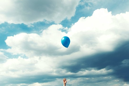 Low Angle View Of Cropped Hand With Blue Balloon Against Cloudy Sky