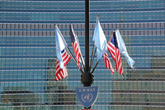 Low Angle View Of American Flags And United Nations Flags Against Modern Building