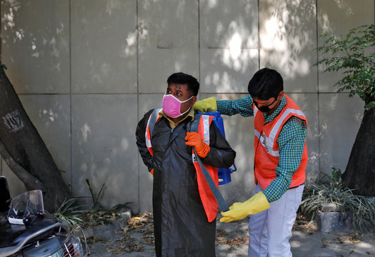 Dev Dutt Sharma, a sanitation worker, gets ready with the help of a colleague, during an extended nationwide lockdown to slow the spread of the coronavirus disease (COVID-19), in New Delhi