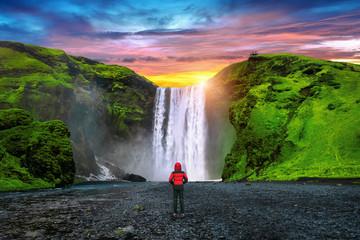 Wall Mural - Skogafoss waterfall in Iceland. Guy in red jacket looks at Skogafoss waterfall.