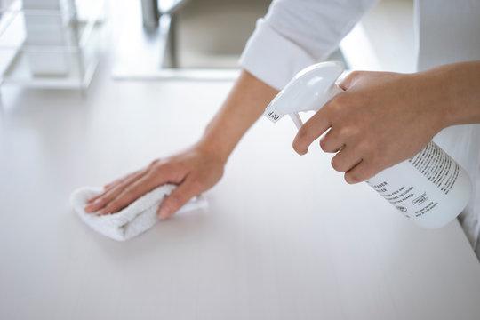 除菌スプレーで拭き掃除をする女性の手元