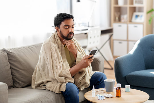 health, cold and people concept - sick young indian man in blanket with smartphone at home