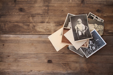 old vintage monochrome photographs in sepia color are scattered on a wooden table, the concept of genealogy, the memory of ancestors, family ties, memories of childhood Wall mural