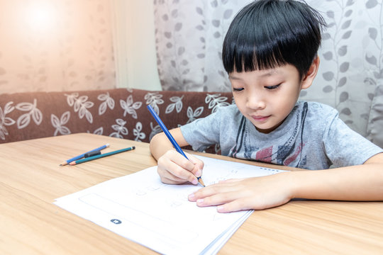 Little boy writing homework on wooden table at home. Kid learing and writing alphabet looking very happy.