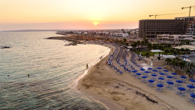 Aerial view of coastline sunset and landmark beach of Agia Thekla, Ayia Napa, Famagusta, Cyprus from above. Bird's eye skyline view of tourist attraction golden sand bay, islet, sunbeds in Ammochostos