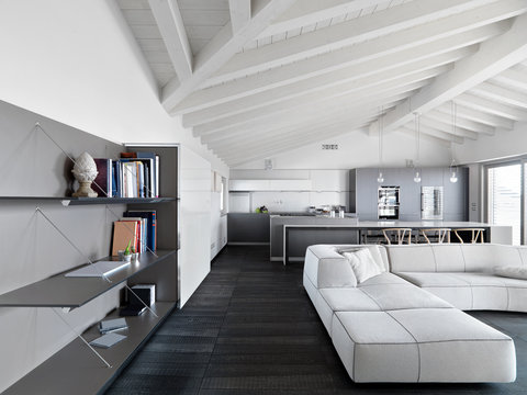 modern living room interior in the attic room with wooden floor and ceiling with exposed wooden beams, on the right side there is a sofa, in the background the kitchen with island kitchen