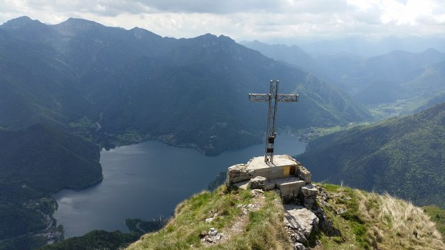 High Angle View Of Cross On Cliff Against Mountains