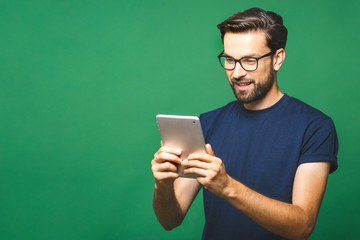 Happy young man in casual shirt and glasses standing and using tablet over green background