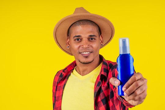 afro brazilian man choosing spf bottle in studio yellow wall