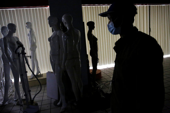 A worker wearing a face mask is seen next to mannequins inside an empty clothing store after it went out of business following the coronavirus disease (COVID-19) outbreak, in Beijing