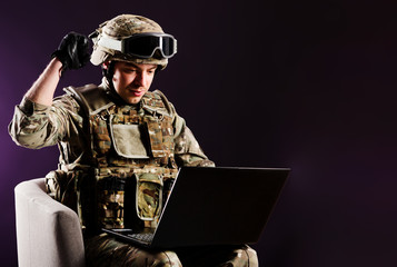 Man gamer with laptop is celebraiting the win in soldier clothes on brown background. Concept of win.