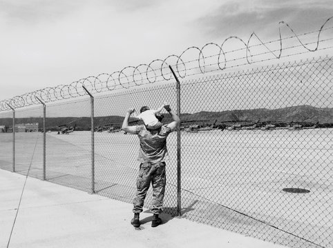 Rear View Full Length Of Soldier Carrying Child By Fence At Marine Corps Base Camp Pendleton