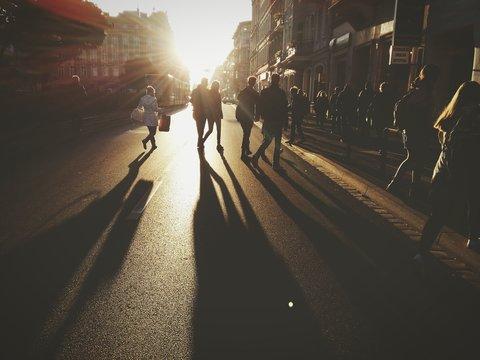 People Walking On City Street Against Bright Sky