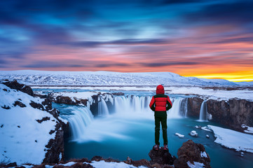 Wall Mural - Godafoss waterfall at sunset in winter, Iceland. Guy in red jacket looks at Godafoss waterfall.