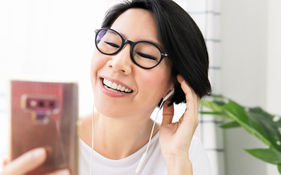 Beautiful middle aged Asian woman smile, talk and online video call with family and friends with smartphone at home during pandemic of Covid-19, city lockdown, work from home and social distancing