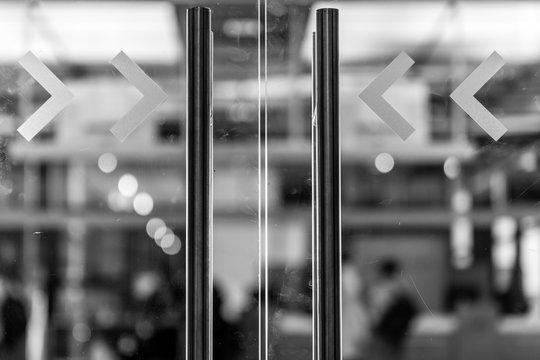 Close-up Of Arrow Symbols On Glass Door