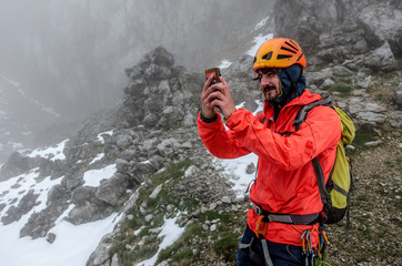 Man Playing Pokémon Go On Rocky Mountain