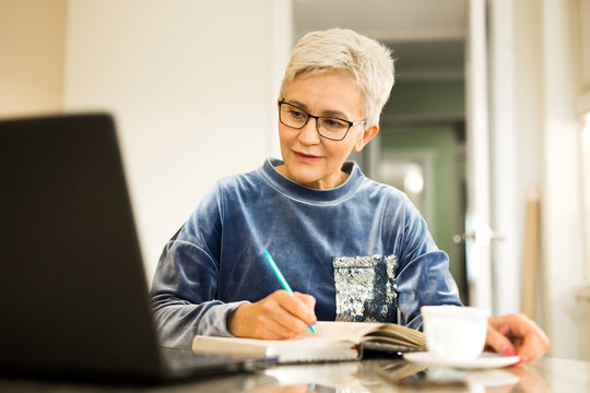 stylish woman with a short haircut sits at a table with a laptop