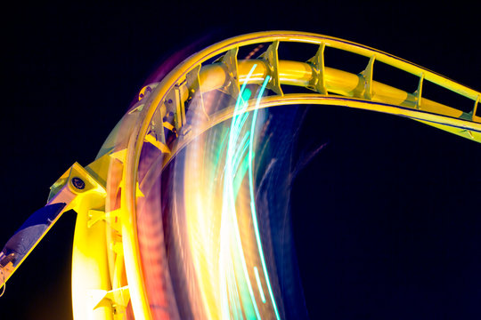 Low Angle View Of Illuminated Rollercoaster At Night