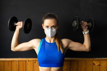 Young fit woman with n96 face mask  doing shoulder press exersice at the gym with dumbbells. Fitness strength workout under coronavirus health crisis.