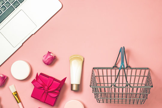 Concept of online shopping cosmetics. Top view on cosmetics bottles, cream, soap, makeup brushes, mobile phone on a pink background, flat lay, frame