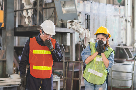 Asian female engineer wearing hygienic mask protect with helmet safety looking male engineer sneezing into his hands in factory Industrial.Coronavirus Protective, Safety Concept