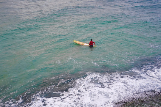One Surfer man in a red jacket with a yellow surfboard in the azure ocean.