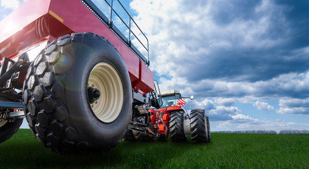 Fototapete - Back view of modern tractor with cart on a agricultural field