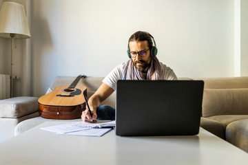 Contemporary man with guitar writing chords in living room