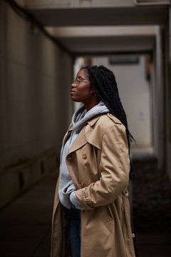 Side view of young beautiful African American female with braids in casual outfit and glasses looking away while standing in hallway of contemporary building