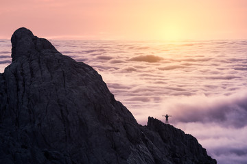 Silhouette of unrecognizable person stretching arms standing on peak of rough cliff with colorful clouds on background during sunset