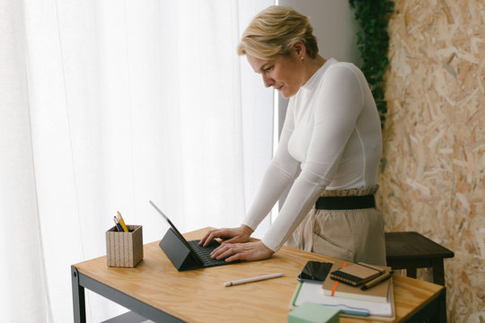 Focused blond adult woman standing at wooden table with stationery typing on portable keypad of tablet against light window