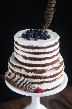 From above of yummy rustic chocolate naked cake with white cream decorated with blueberries and bird feathers on white cake stand against black background