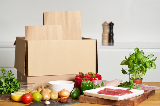 Box with packed meat vegetables on kitchen background. Food delivery services during coronavirus pandemic and social distancing. Shopping online. .Dinner delivery service.