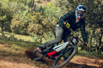 Unrecognizable man looking at camera in helmet, gloves and protection glasses jumping doing whip trick downhill during mountain biking practice in wood forest
