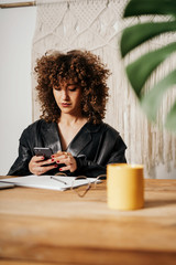 Positive retro businesswoman with curly hair sitting at table and using smartphone in office