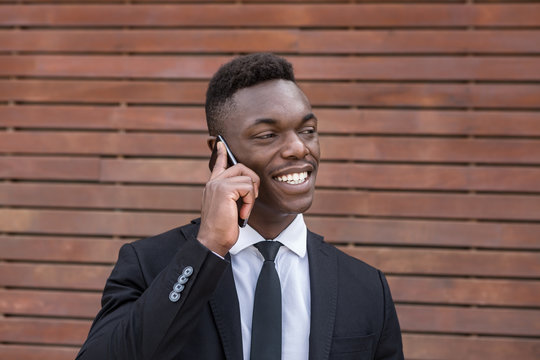 Positive smiling successful African American male speaking on mobile phone and holding finger in pocket while standing beside urban striped wooden wall