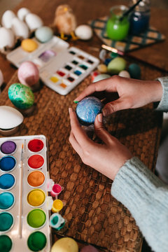 From above anonymous person wrapping egg into film to make ornament over table while preparing for Easter celebration at home