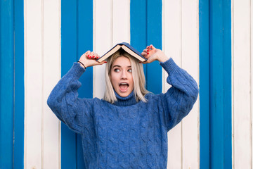 Funny astonished young female in casual knitted sweater holding open book on head and looking away while standing against colorful wall