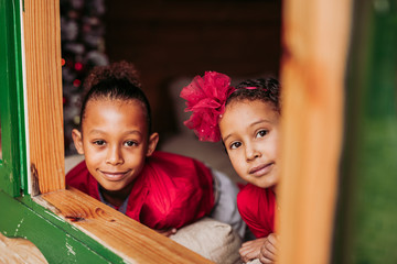 Cute black little siblings smiling and looking at camera through open window of wooden cabin