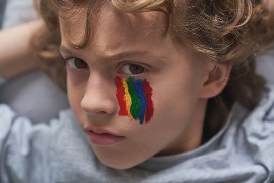 Unhappy boy with rainbow under eye looking at camera at home during quarantine