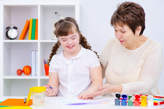 A girl with down syndrome is engaged in creativity with her mother at home. Education for disabled children concept.