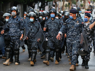 Lebanese police wear face masks as they walk together, during a protest against the collapsing Lebanese pound currency near Lebanon's Central Bank in Beirut