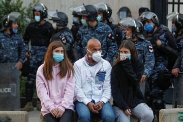 Lebanese demonstrators wear face masks during a protest against the collapsing Lebanese pound currency outside Lebanon's Central Bank in Beirut