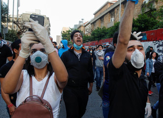 Lebanese demonstrators wear face masks as they chant slogans during a protest against the collapsing Lebanese pound currency outside Lebanon's Central Bank in Beirut