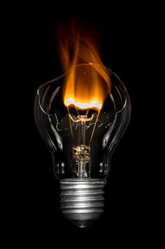 Close-up Of Broken Light Bulb Burning Against Black Background