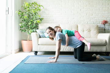 Little girl working out with her mom