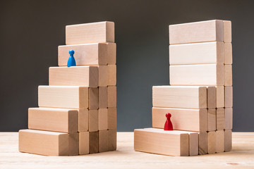 Steps made of wooden blocks. The blue pawn follows a simple and quick path. The red pawn has a difficult insurmountable barrier. Different difficulty level, injustice, concept.