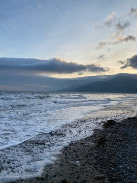 Pebble beach at dusk with Mourne Mountains in background.