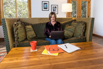 Happy middle age woman working from home on a laptop computer while sitting on a comfortable sofa at a coffee table with a coffee cup, notebook and file folders